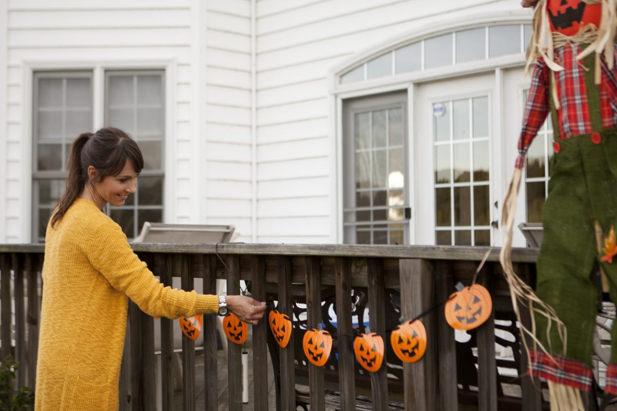 Women decorating around house for Halloween.